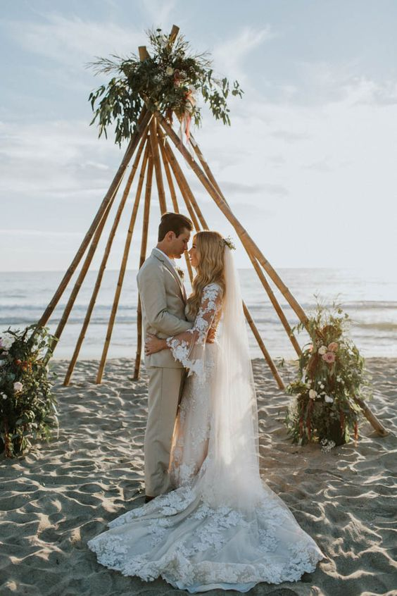 trendy teepee-like wedding arbor with greenery and blooms on each corner for a bold look