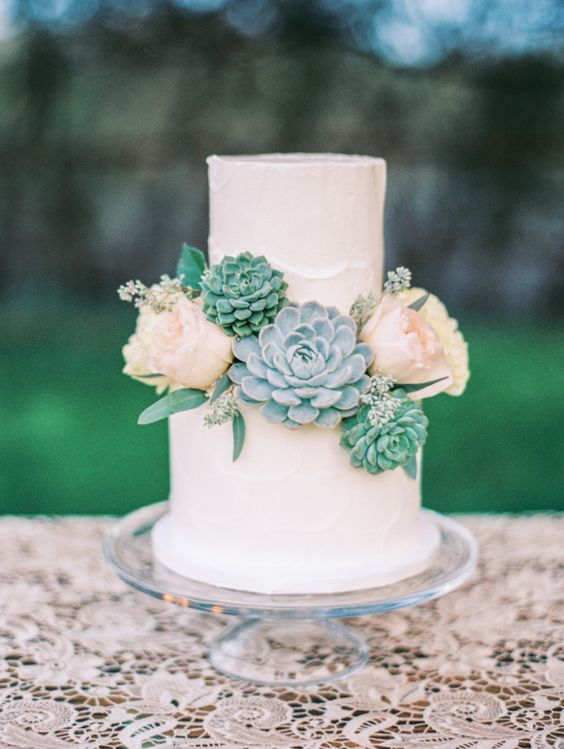 a buttercream wedding cake with neutral blooms and several blooms for decor