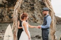 24 a driftwood wedding arch shaped as a surf for a creative beach ceremony look