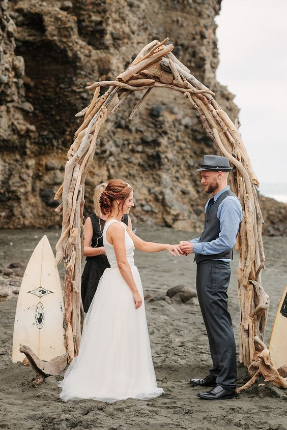 a driftwood wedding arch shaped as a surf for a creative beach ceremony look
