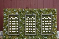 24 a moss and succulent wall is used for displaying escort cards in frames, what a modern idea