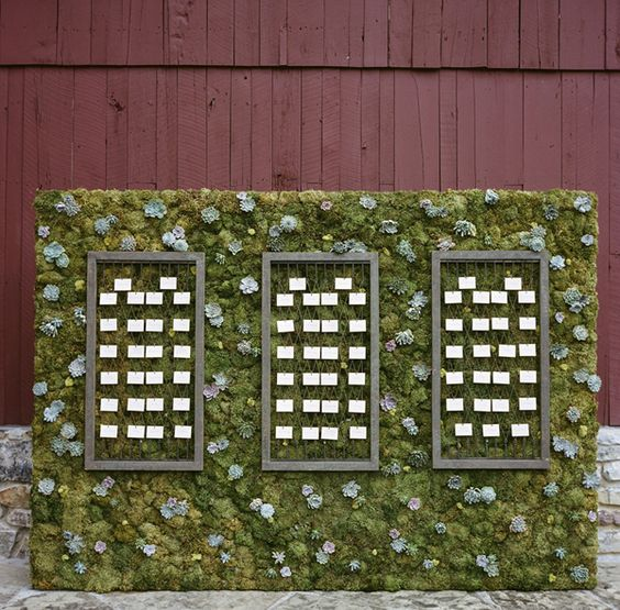a moss and succulent wall is used for displaying escort cards in frames, what a modern idea