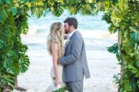 24 a super lush tropical wedding arch of driftwood and lush tropical leaves
