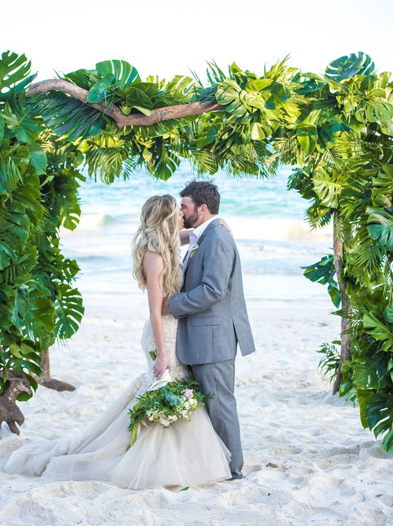 a super lush tropical wedding arch of driftwood and lush tropical leaves