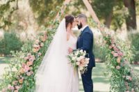 24 a whimsy triangle wooden arch with lush greenery and pink flowers coming up the arch