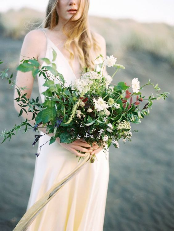 a wildflower wedding bouquet with textural greenery, white blooms and various herbs