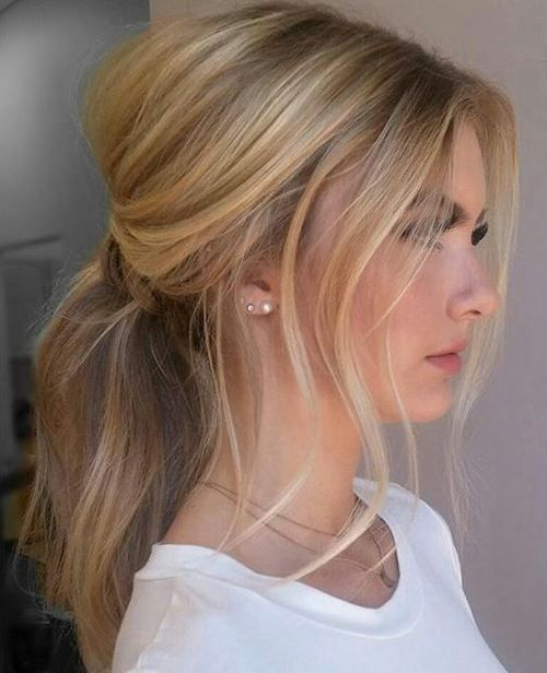 a chic messy and wavy low ponytail with some locks down and a small bump for a chic casual look