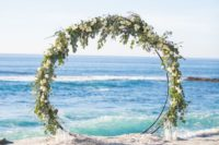 25 a giant circle wedding arch decorated with white blooms and greenery and with candles around