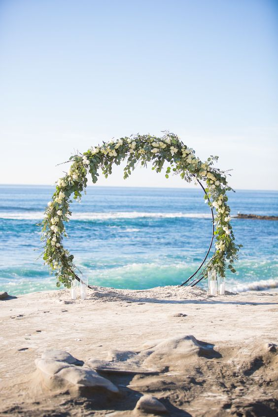 a giant circle wedding arch decorated with white blooms and greenery and with candles around