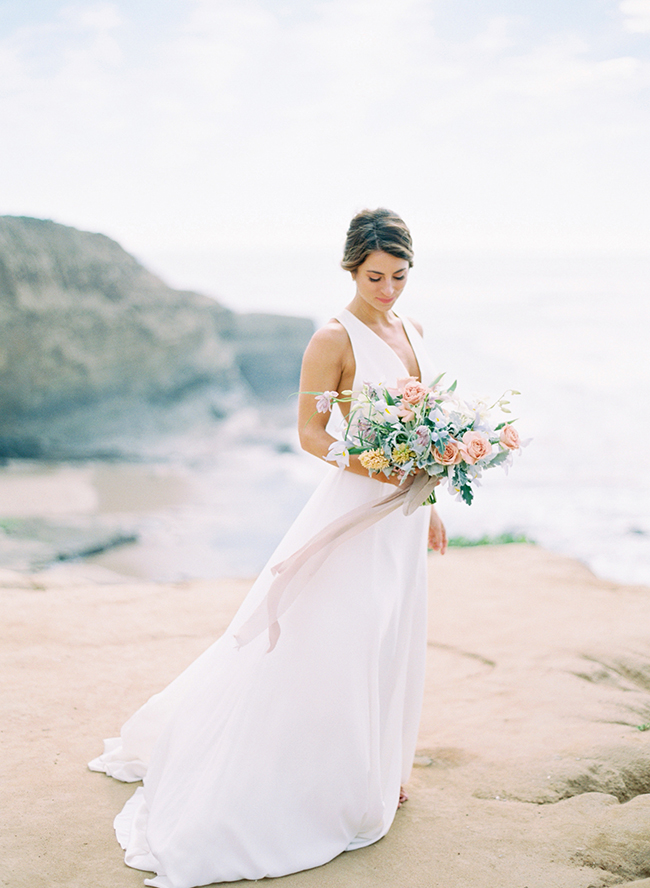a modern A-line wedding dress with thick straps, a plunging neckline for a modern beach bride
