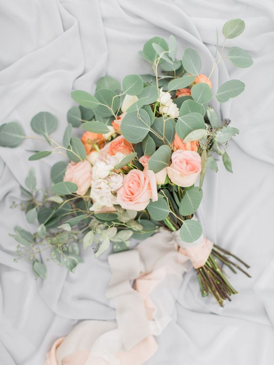 a simple wedding bouquet with blush and coral roses and eucalyptus with blush ribbons is a simple and cute piece