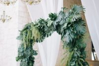 25 a tropical wedding arch covered with tropical leaves and hanging greenery plus glam chandeliers over it