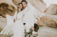 25 a unique wedding dress with a cutout, a front slit, a long train and long fringed sleeves