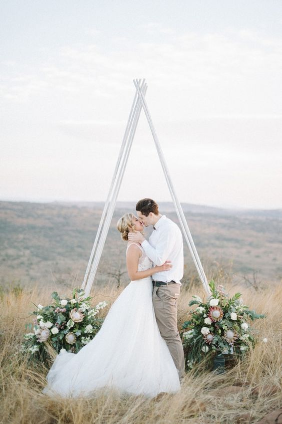 a white triangle wedding arbor with lush greenery and large blooms at the base looks very eye-catchy