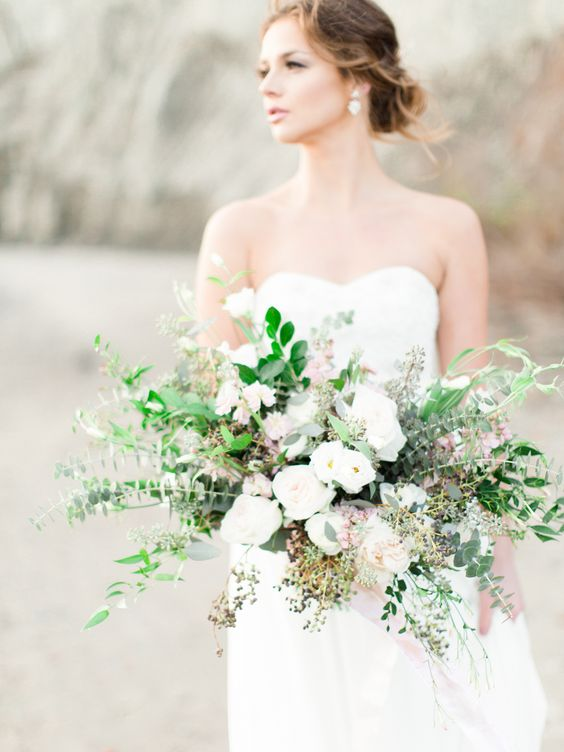 an organic wedding bouquet with various greenery and white flowers for a coastal wedding