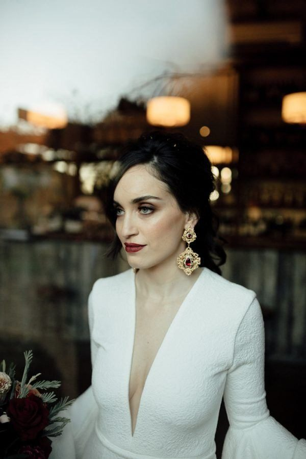 a moody bride rocking statement vintage earrings of gold and rubies and a matching lip