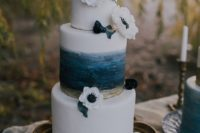 26 a seaside wedding cake with a brushstroke navy and gold tier and white anemones