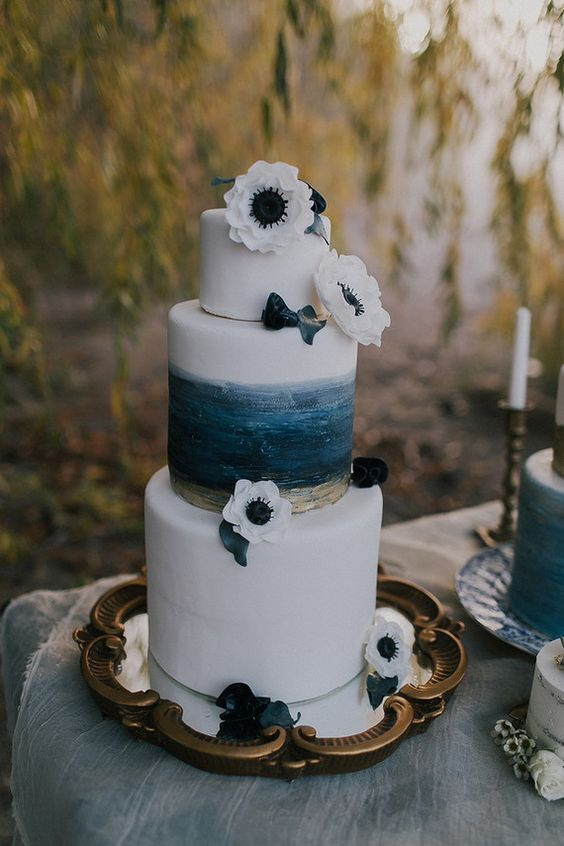a seaside wedding cake with a brushstroke navy and gold tier and white anemones