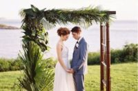 26 a tropical wedding arch with lush tropical greenery on one side
