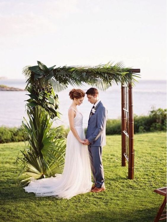 a tropical wedding arch with lush tropical greenery on one side