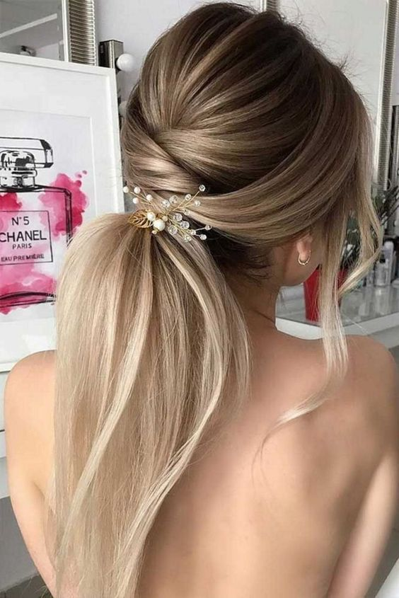 a twisted low ponytail with a volume, some locks down and a pretty hairpiece with crystals