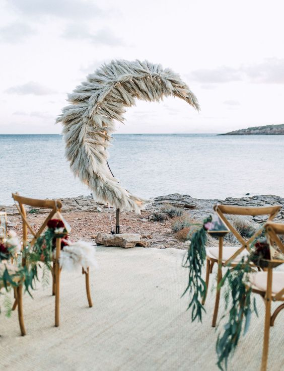 a unique half moon pampas grass wedding altar for a romantic beach or coastal wedding