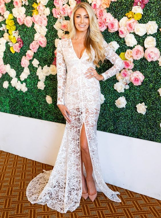 an ivory lace dress with long sleeves, a front slit, a deep V-neckline and a small train