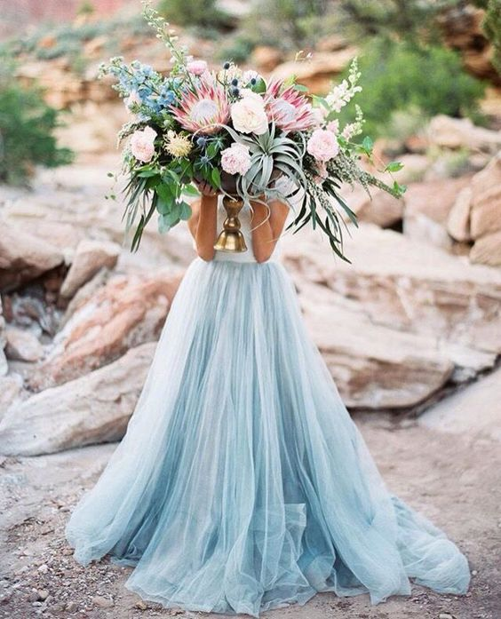 an oversized coastal wedding bouquet with air plants, blush and blue blooms and king proteas