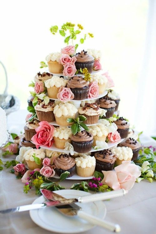 serve cupcakes on a stand decorated with greenery and fresh blooms to make the stand feel garden like