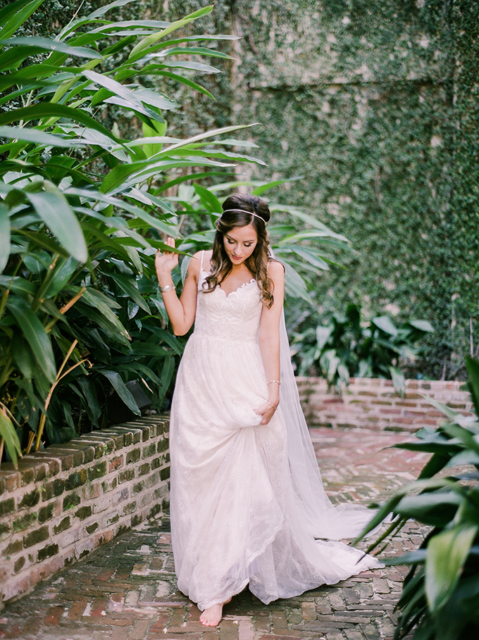 The bride opted for a chic lace spaghetti strap wedding dress with an A-line skirt, an embellished headpiece with a long veil