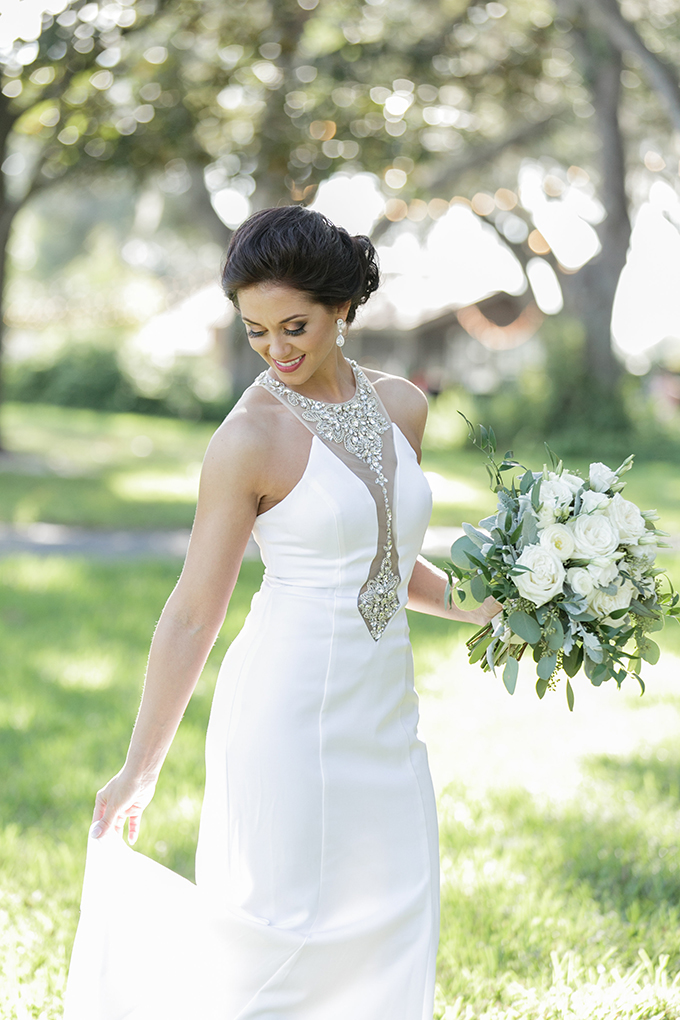 The bride was wearing a fantastic vintage sheath wedding gown with an embellished illusion neckline and statement earrings