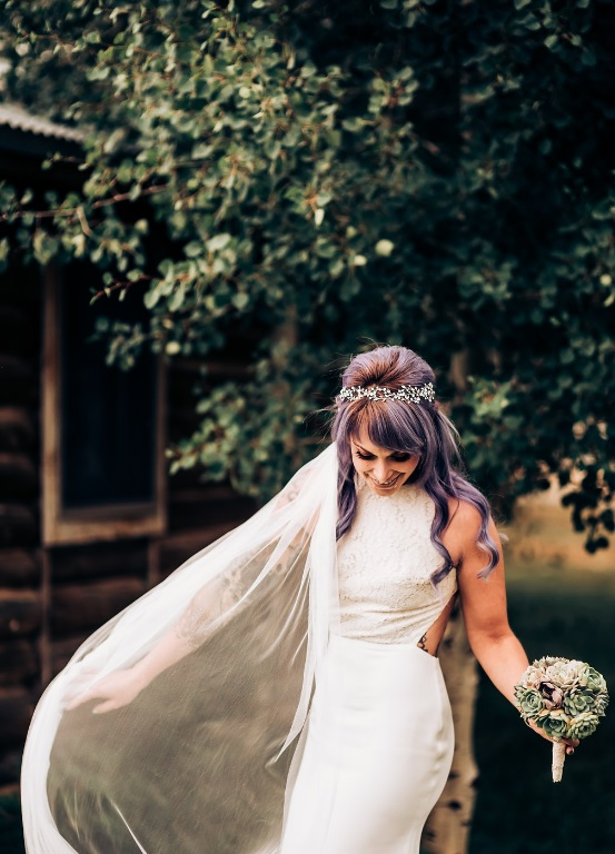 The bride was wearign a sheath wedding dress with a halter neckline, a lace bodice and a plain skirt