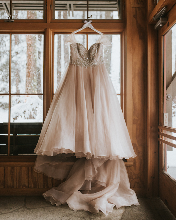 The bride was wearing a beautiful blush off the shoulder A-line wedding gown with a long train and an embellished bodice