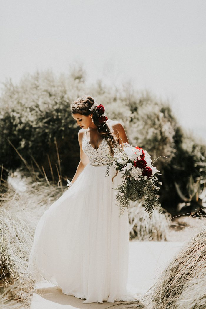 The bride was wearing a fantastic wedding gown with an embellished bodice on spaghetti straps and a fishtail braid with fresh blooms