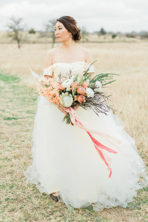 The bride was wearing an ivory off the shoulder wedding dress with a plain bodice and a layered full skirt