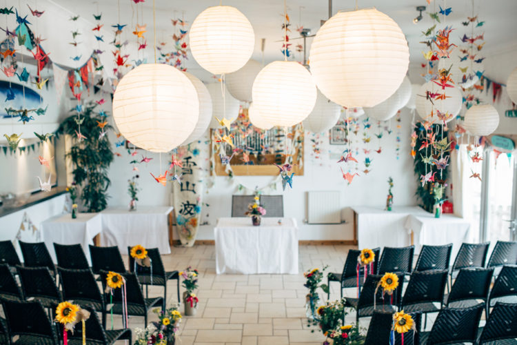 The ceremony space was done with colorful origami paper cranes, paper lamps and decorated with fresh blooms, mostly sunflowers