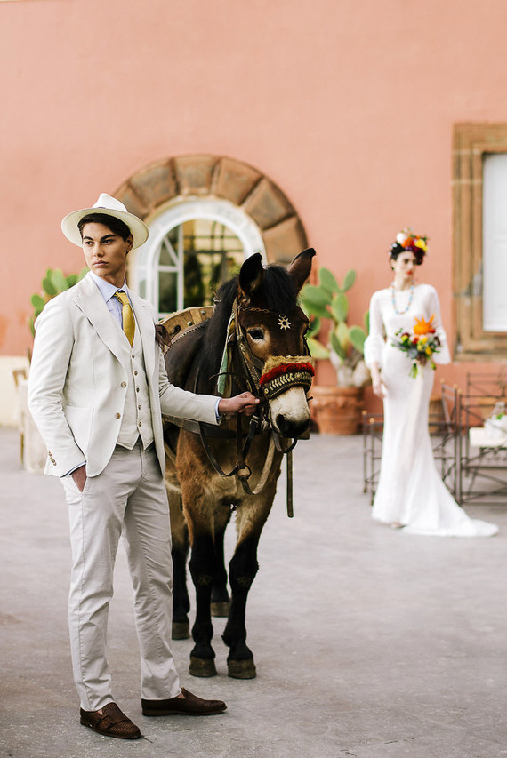 The groom was wearing a creamy suit with  a yellow tie, a hat and brown moccasins