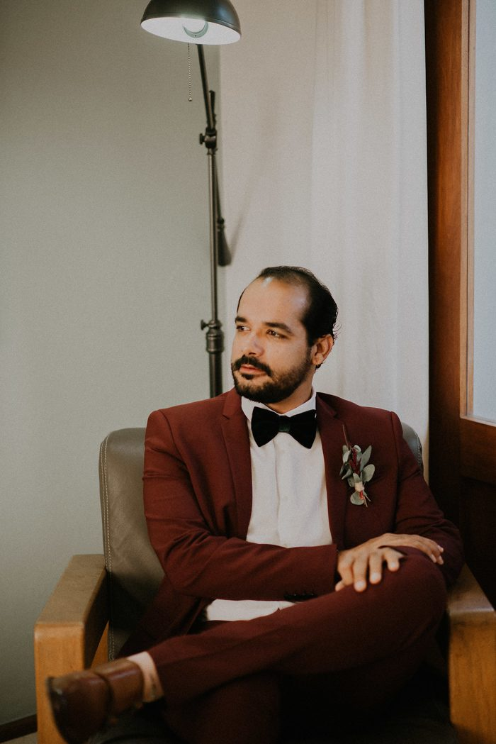 The groom was wearing an elegant burgundy suit with a black bow tie and brown shoes
