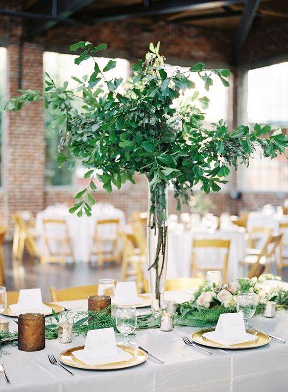 a lush greenery centerpiece of branches and leaves is a chic idea to stand out without any blooms