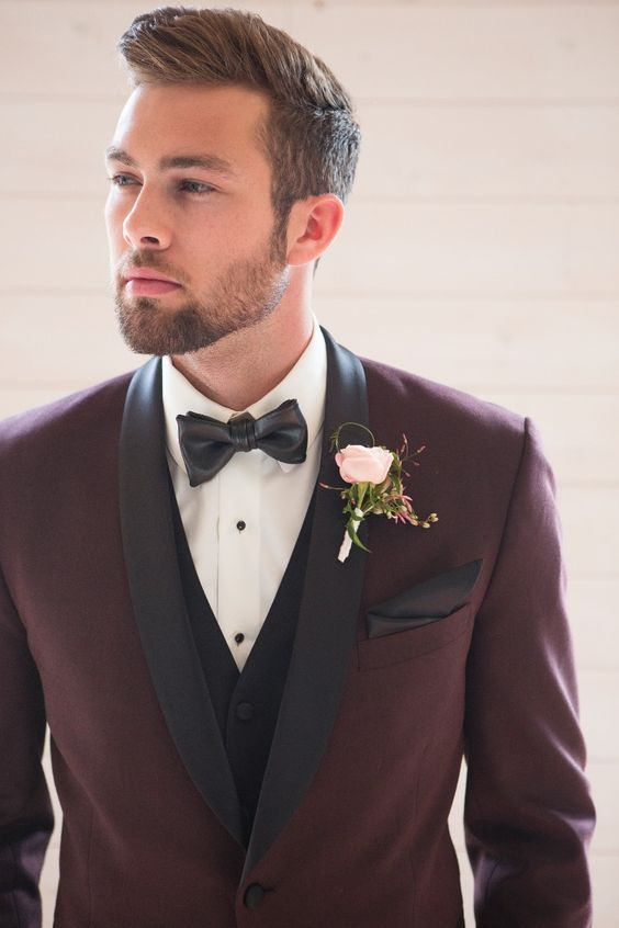 a stylish take on a tuxedo look   a burgundy tux with black lapels and a black vest