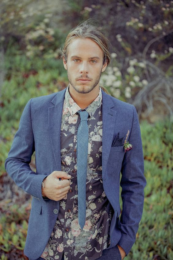 slate blue suit, a blue tie, a dark floral shirt create a unique relaxed and unusual look