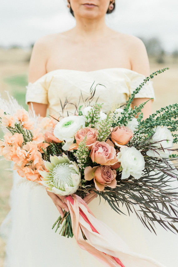 Her bouquet was done with white and rust-colored blooms, greenery and herbs plus king proteas