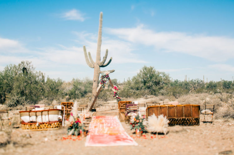 The ceremony space was a very boho one, with a colorful runner, pampas grass and bold flowers