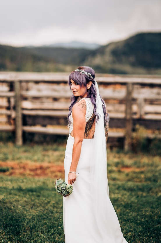 The cutout back showed off the bride's tattoos, and her pastel hair was highlighted with a rhinestone hairpiece and a long veil