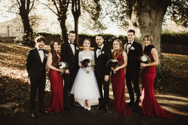 The groom and groomsmen were wearign black tuxedos, and the bridesmaids were rocking burgundy mermaid dresses and faux fur scarves