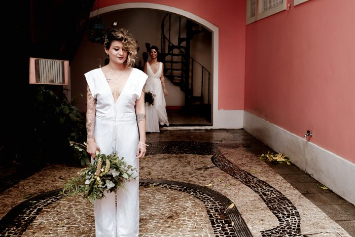 The second bride was wearing a modern jumpsuit with a plunging neckline, cap sleeves and a cool headpiece