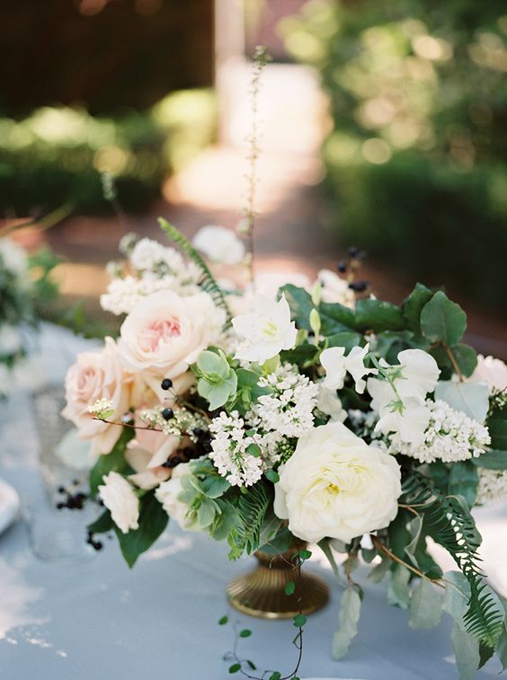 a fresh and lush floral centerpiece with white and blush blooms and greenery looks very cool