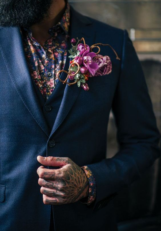 a navy three piece suit, a dark floral shirt and a bold pink floral boutonniere for an edgy moody look
