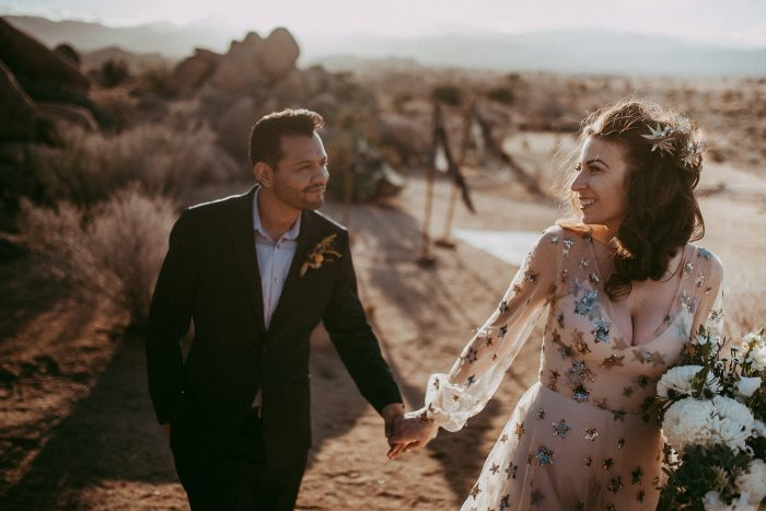 The bride was rocking a fantastic blush wedding dress with long sleeves and a deep V-neckline all covered with sequin stars