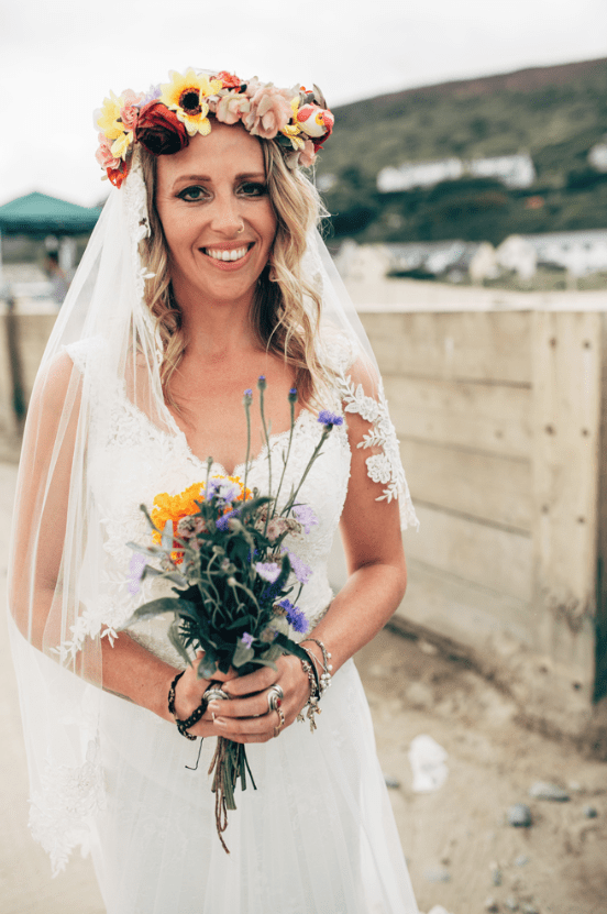 The bride was wearing a lace thick strap wedding dress, a DIY floral crown and carrying a colorful widlflower bouquet